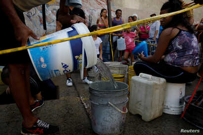 Locals queue to collect water from an underground water main pipeline in Caracas, Venezuela, April 1, 2019.