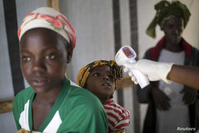 FILE - A health worker checks the temperature of a girl at the entrance to a Red Cross facility in the town of Koidu, Sierra Leone.