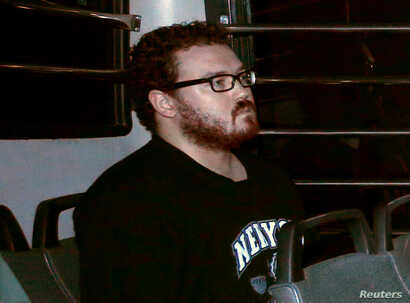 FILE - Rurik George Caton Jutting, a former British banker charged with two counts of murder sits in the back row of a prison bus as he arrives at the Eastern Law Courts in Hong Kong, Nov. 24, 2014.