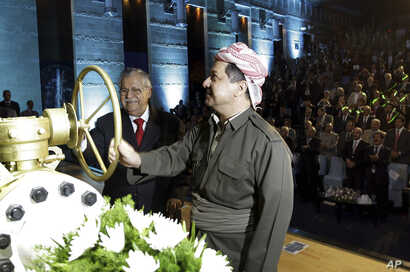 FILE - Kurdish president Massud Barzani (R), and Iraqi President Jalal Talabani open a ceremonial valve during an event to celebrate the start of oil exports from the autonomous region of Kurdistan, in the northern Kurdish city of Irbil, June 1, 2009...