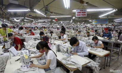 FILE - Laborers work at a garment factory in Bac Giang province, near Hanoi, Oct. 21, 2015. Vietnam's textiles and footwear would gain strongly from the Trans-Pacific Partnership, after exports of $31 billion last year for brands such as Nike, Adidas...