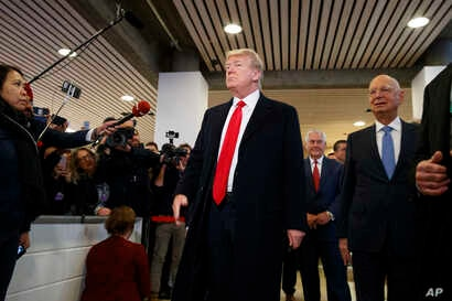 President Donald Trump talks with reporters as he arrives at the World Economic Forum, Jan. 26, 2018, in Davos.
