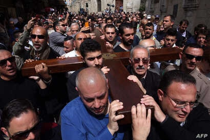 Local Arab Christian pilgrims carry a wooden cross along the Via Dolorosa (Way of Suffering) in Jerusalem's Old City during the Good Friday procession on March 25, 2016.
