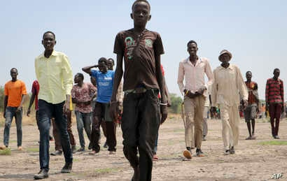 In this photo taken May 2, 2018, men walk over to greet a humanitarian aid team in Kandak, South Sudan.