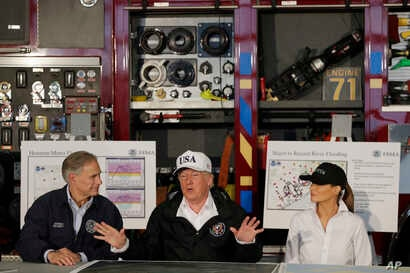 President Donald Trump, flanked by Texas Gov. Greg Abbott and first lady Melania Trump speaks during a briefing on Harvey relief efforts, Aug. 29, 2017, at Firehouse 5 in Corpus Christi, Texas.