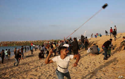 Protesters gather while others hurl stones at Israeli troops near the fence of the Gaza Strip border with Israel during a protest on the beach near Beit Lahiya, northern Gaza Strip, Nov. 19, 2018.