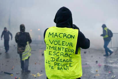 """A demonstrator wearing a yellow jacket reading """"Macron, thief, lier, crook, go away, the people banishes you"""" near the Champs-Elysees avenue during a demonstration Saturday, Dec.1, 2018 in Paris."""