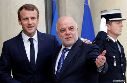 French President Emmanuel Macron welcomes Iraqi Prime Minister Haider Al-Abadi at the Elysee Palace in Paris, Oct. 5, 2017.