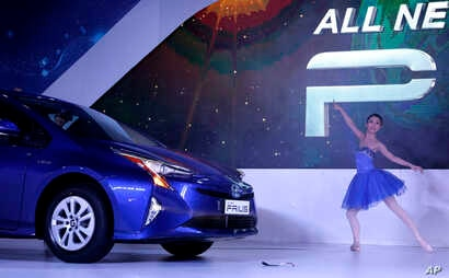A performer dances as Toyota's 4th generation Prius Hybrid car is launched at the Auto Expo in Greater Noida, near  New Delhi, India, Feb. 4, 2016.