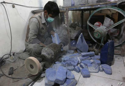 An Afghan man works at a lapis lazuli factory in the city of Kabul, Afghanistan. An international anti-corruption watchdog says Afghanistan's war is being fueled by the country's mining sector, with the Taliban earning up to $20 million a year from i...