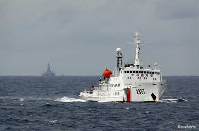 FILE - A Chinese Coast Guard vessel, with the disputed oil rig in the background, is seen in the South China Sea  June 13, 2014.