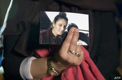 FILE - A picture of Shamima Begum is held by her sister, who was being interviewed by reporters in central London, Feb. 22, 2015. Britain last week revoked nationality of Shamima Begum, a 19-year-old woman of Bangladeshi heritage who joined IS in Sy...