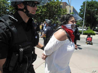 Police officers take a woman into custody after a campaign rally for Republican presidential candidate Donald Trump in Fresno, Calif., May 27, 2016.