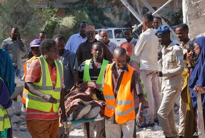 Somalis carry away the body of a civilian victim who was shot dead by gunmen during a suicide car bomb attack on a government building in Mogadishu, Somalia, March 23, 2019.