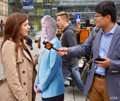 """A foreign reporter interviews a local German journalist in Berlin on what reactions she has been getting to 'Angela Merkel.' """"Most people laugh,"""" she says. (Photo: J. Dettmer / VOA)"""