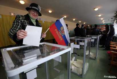 A woman holds a Russian flag as she casts her ballot during the referendum on the status of Ukraine's Crimea region at a polling station in Bakhchisaray, Crimea, Ukraine, March 16, 2014.