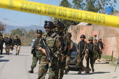 Pakistani soldiers cordon off the area of suicide bombing in Charsadda, Pakistan, Feb. 21, 2017. Police say three suicide bombers  attacked a courthouse in northwestern Pakistan