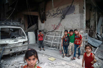 Children are seen near rubble of damaged buildings in the eastern Damascus suburb of Ghouta, Syria, July 17, 2017.