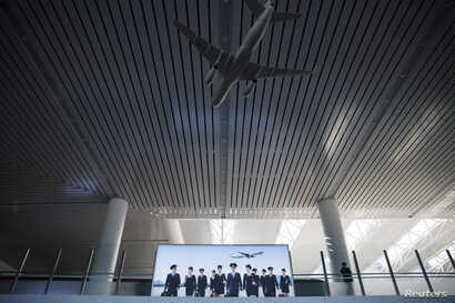 FILE - A man stands by an advertisement for North Korean airliner Air Koryo inside Pyongyang's airport, Oct. 12, 2015.