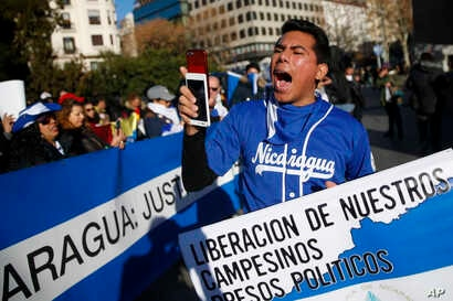"""A demonstrator shouts slogans behind a banner reading in Spanish: """"Release of our farmers Political prisoners"""" and """"Nicaragua: Justice"""" during a protest against the Nicaraguan government in Madrid, Spain, Jan. 12, 2019."""