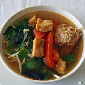 Linh Nguyen's Vietnamese soup features fried tofu, tomatoes, a scattering of fresh herbs and some delicate poached crab and pork dumplings.