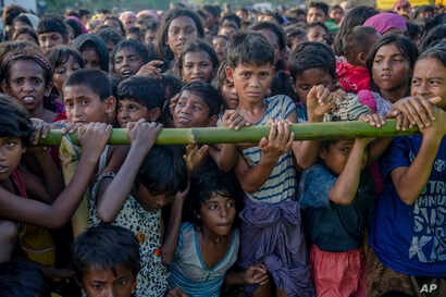 Rohingya Muslim children, who crossed over from Myanmar into Bangladesh, wait to receive aid during a distribution near Balukhali refugee camp, Bangladesh, Sept. 25, 2017.