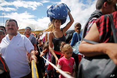 FILE - A woman carrying a bundle on her head waits in line to cross the border into Colombia through the Simon Bolivar International Bridge in San Antonio del Tachira, Venezuela, July 17, 2016.