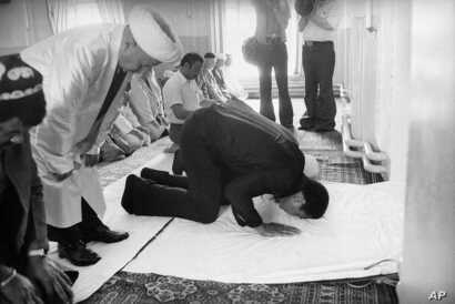 FILE - Then-U.S. heavyweight boxing champ Muhammad Ali prays at a mosque during his 12-day visit to the Soviet Union in June 1978.
