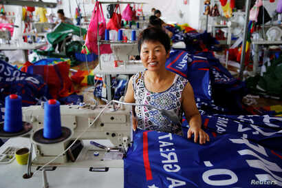 """A worker poses for pictures as she makes flags for U.S. President Donald Trump's """"Keep America Great!"""" 2020 re-election campaign at Jiahao flag factory in Fuyang, Anhui province, China, July 24, 2018."""