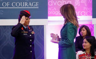 First lady Melania Trump receives a salute as she presents an award to Jordanian police officer Colonel Khalida Khalaf Hanna al-Twal during the International Women of Courage (IWOC) celebration at the State Department in Washington, U.S., March 7, 20...