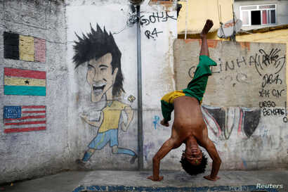 A member of the Acorda Capoeira (Awaken Capoeira) group prepares for a performance for tourists in the Rocinha favela in Rio de Janeiro, Brazil, July 25, 2016.