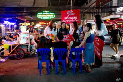Pauline Ngarmpring, left, speaks with workers of a roadside massage parlor during an election campaign in Bangkok, Feb. 13, 2019.
