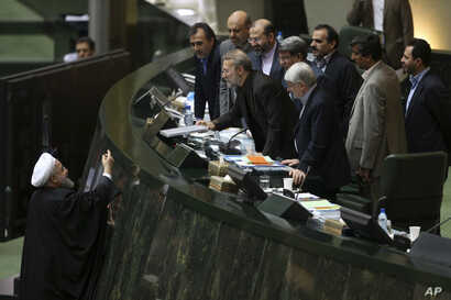 Iranian President Hassan Rouhani, left, presents a draft of the country's new budget and sixth development plan to the parliament speaker Ali Larijani in an open session of parliament, in Tehran, Iran, Jan. 17, 2016.