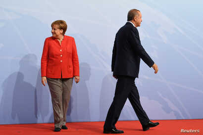 German Chancellor Angela Merkel and Turkey President Recep Tayyip Erdogan go their separate ways after a handshake greeting at the beginning of the G20 summit in Hamburg, Germany, July 7, 2017.