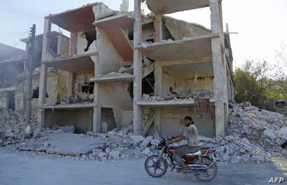 A Syrian man rides a motorcycle past a destroyed building in an area that was hit by a reported airstrike in the district of Jisr al-Shughur, in the Idlib province, Sept. 4, 2018.