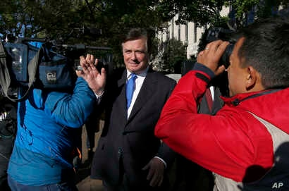 Paul Manafort makes his way through television cameras as he walks from Federal District Court in Washington, Oct. 30, 2017.