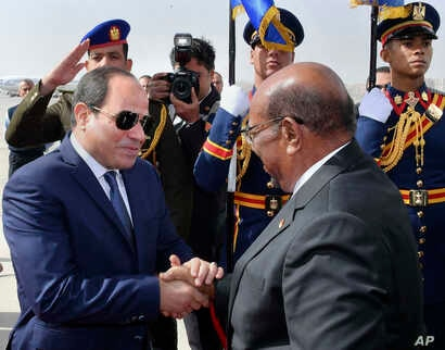 In this photo released by the Egyptian Presidency's office, Sudan's President Omar al-Bashir right, shakes hands with Egyptian President Abdel-Fattah El-Sissi in Cairo, Egypt, Jan. 27, 2019.