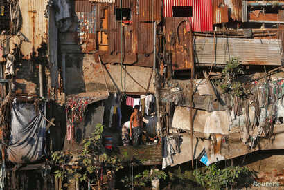 A man brushes his teeth outside a shanty in Dharavi, one of Asia's largest slums, in Mumbai, India, Dec. 27, 2016.