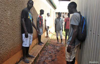 Residents gather to look at the footprints and traces of struggle, outside the house where an Italian volunteer lived before she was seized, in Chakama trading centre of Magarini, Kenya, Nov. 21, 2018.