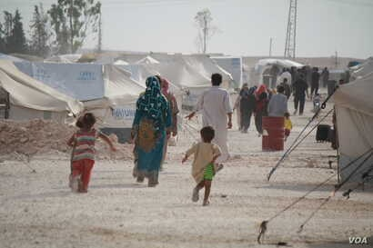Camps for displaced persons in Syria are notoriously short of food, clean water and health care, with some fleeing urban families saying they prefer to face stigma in villages than endure hardship in camps, in Ain Issa, Syria, Aug. 17, 2017. (H. Murd...