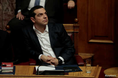 Greek Prime Minister Alexis Tsipras attends a parliamentary session before a vote on setting up a special committee which will probe the role of ten politicians in a case which involves alleged bribery by Swiss drugmaker Novartis, in Athens, Greece, ...