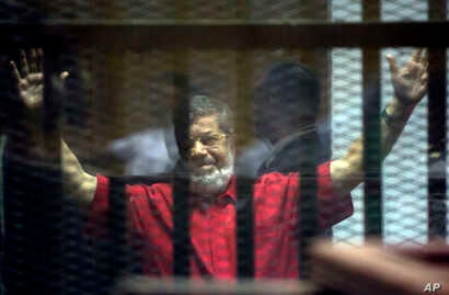 Former Egyptian President Mohamed Morsi, wearing a red jumpsuit that designates he has been sentenced to death, raises his hands inside a defendants cage in a makeshift courtroom at the national police academy, in an eastern suburb of Cairo, Egypt, S...
