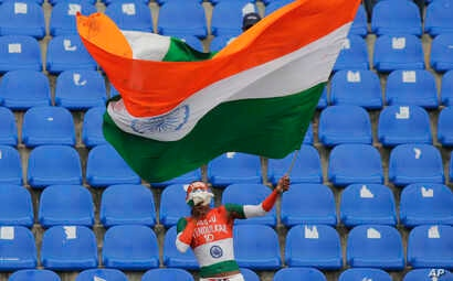FILE - An Indian cricket fan waves the tricolored national flag after India's win over Sri Lanka in the third cricket test match in Pallekele, Sri Lanka, Aug. 14, 2017. Desecrating India's flag is punishable by up to three years in prison.