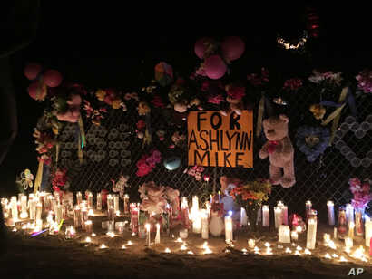 In this May 3, 2016 photo, candles burn at a makeshift memorial for Ashlynne Mike on the Navajo Nation southwest of Farmington, N.M. The FBI said Mike, was abducted after school on Monday, May 2, and her body was found the next day.