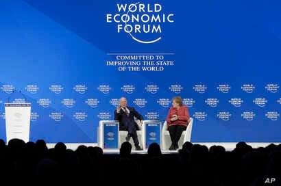 Klaus Schwab, founder and Executive Chairman of the World Economic Forum, talks with German Chancellor Angela Merkel after she addressed the annual meeting of the World Economic Forum in Davos, Switzerland, Jan. 23, 2019.