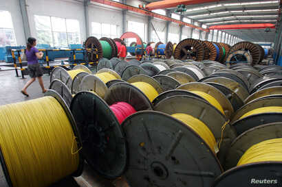 A woman walks in an electricity cable factory in Baoying, Jiangsu province, China, July 23, 2006.