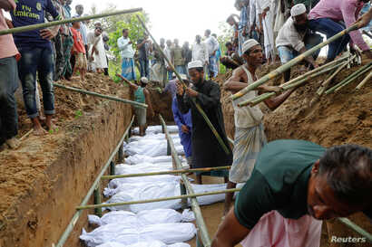 Rohingya refugees who died after their boat capsized, as they were fleeing Myanmar, are buried in a mass grave just behind Inani Beach near Cox's Bazar, Bangladesh, Sept. 29, 2017.