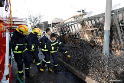 Firefighters work next to burnt vehicles following a blast near a chemical plant in Zhangjiakou, Hebei province, China, Nov. 28, 2018.