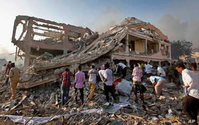 Somalis gather and search for survivors by destroyed buildings at the scene of a blast in the capital Mogadishu, Somalia, Oct. 14, 2017.