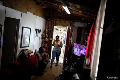 Miguel Rosario Lopez watches a television that works using electricity from a generator on Dec. 11, 2017, while his wife Milagros Jimenez walks through their house, which was partially destroyed by Hurricane Maria.